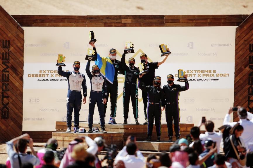 ALULA, SAUDI ARABIA - APRIL 04: Timmy Hansen (SWE), Andretti United Extreme E, Catie Munnings (GBR), Andretti United Extreme E, Johan Kristoffersson (SWE), Rosberg X Racing, Molly Taylor (AUS), Rosberg X Racing, Cristina Gutierrez (ESP), X44, and Sebastien Loeb (FRA), X44, celebrate on the podium during the Desert X-Prix at AlUla on April 04, 2021 in AlUla, Saudi Arabia. (Photo by Zak Mauger / LAT Images)